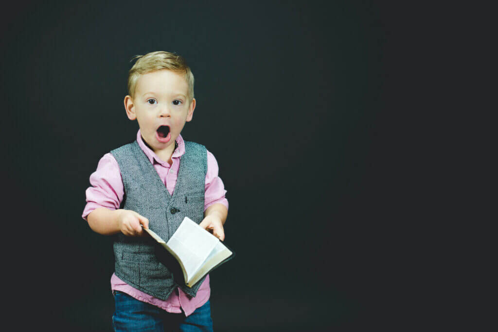 Ein Kind schaut staunend von einem Buch auf: ein Symbolbild für die Spielplatz-Seminare der Michael Bartsch Handelsvertretungen.